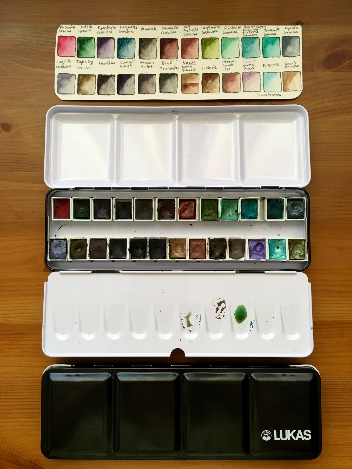 Large black mental watercolor pallet filled with Daniel Smith Watercolor and Lucas metal palette.