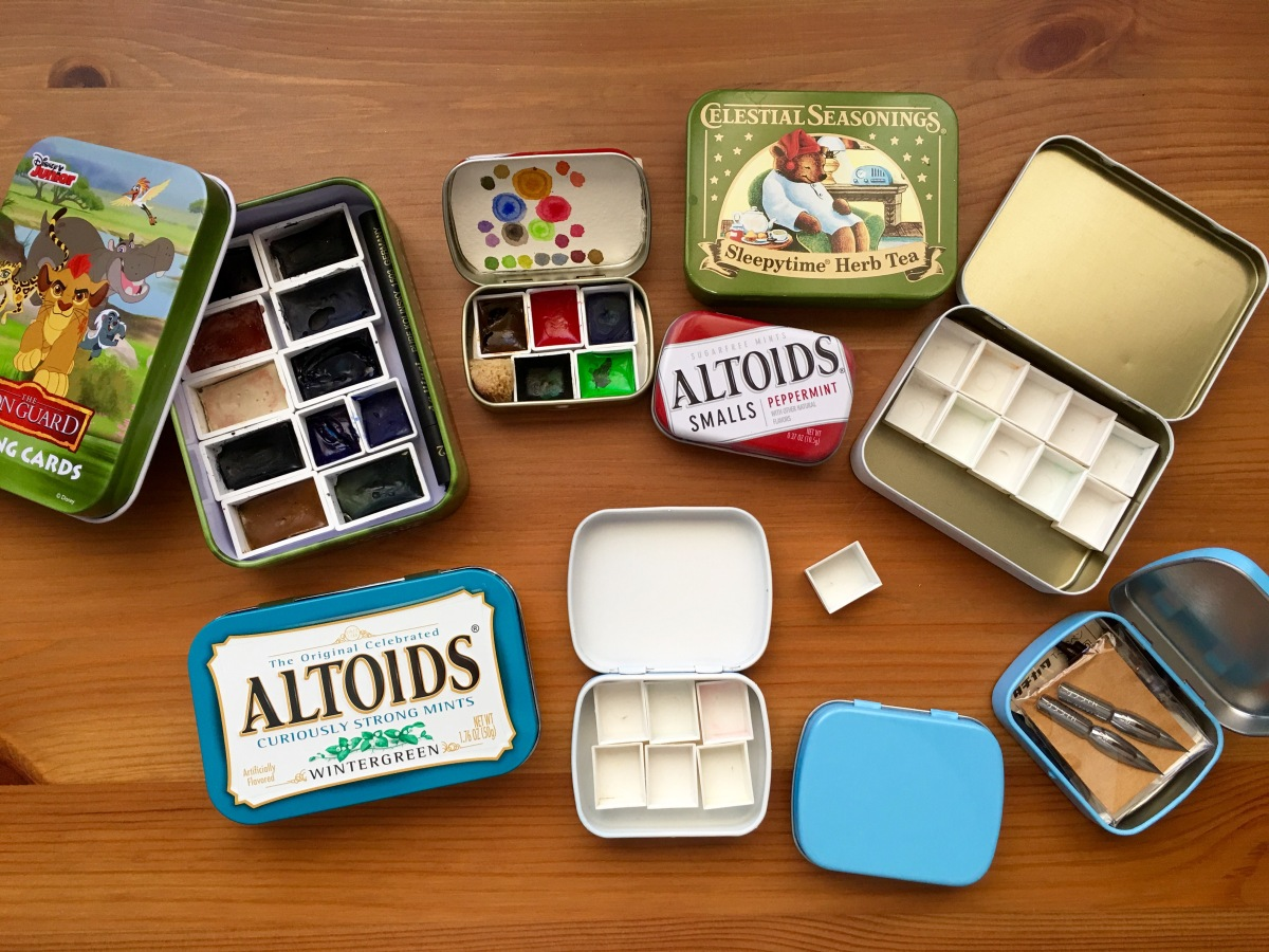 Variety of empty candy, tea, card tins with watercolor half and full pans