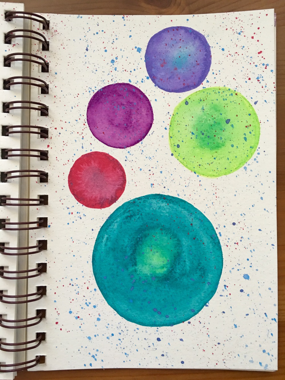 Large dots and splatters done with Caran D'Ache Neocolor II water-soluble was oil pastels