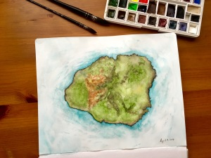 Watercolor aerial view painting of the island of Kauai with paint brushes and a watercolor travel palette filled with half and full watercolour pans