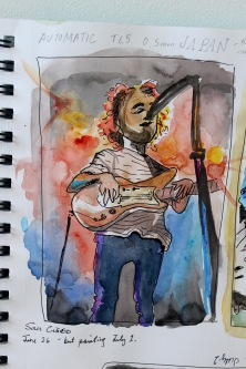 Doodlewash by Sam Orpiada watercolor sketch of musician on stage singing with microphone and playing guitar