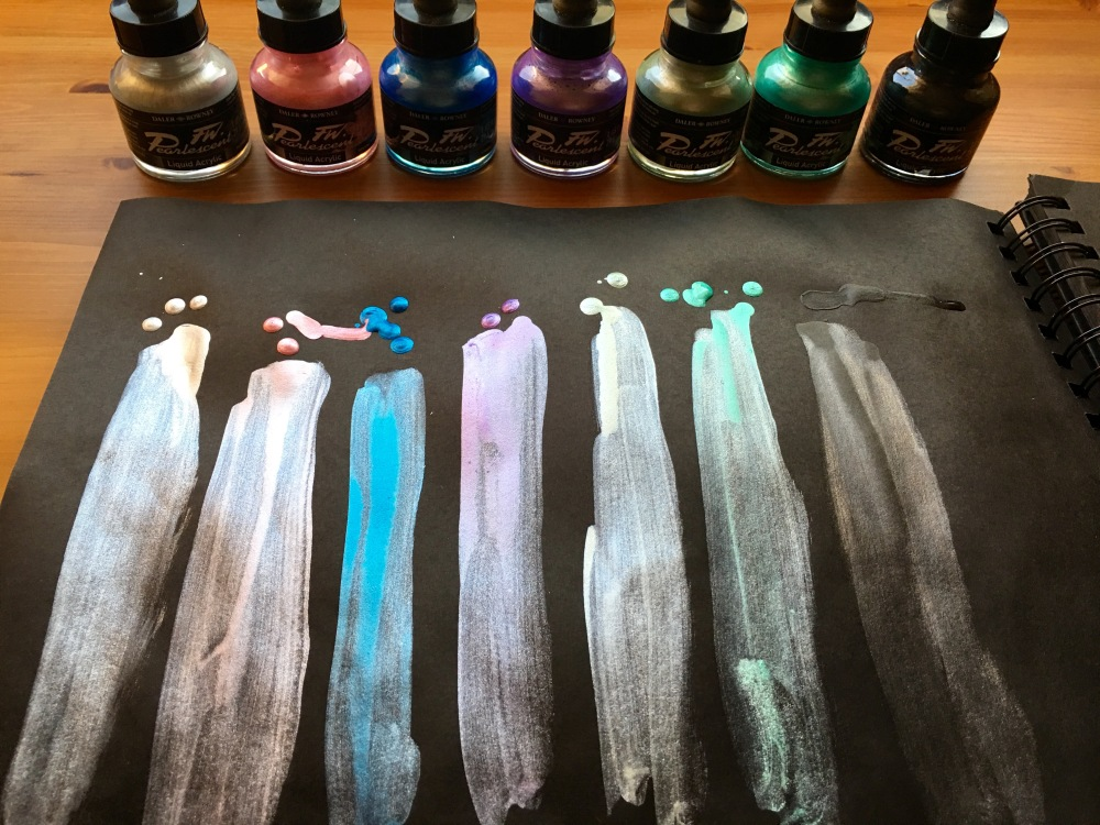 Daler Rowney FW Pearlescent Acrylic Ink swatches silver, pink, blue, purple, green, teal, black in a Derwent Big Book